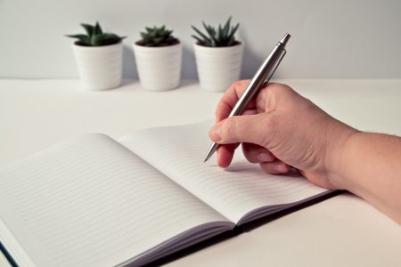 person-holding-silver-retractable-pen-in-white-ruled-book-796603